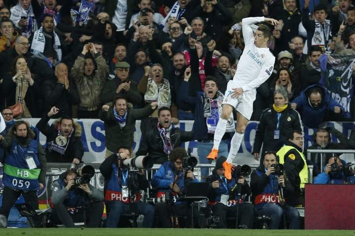 Real Madrid's Cristiano Ronaldo celebrates his side's 2nd goal during a Champions League Round of 16 first leg soccer match between Real Madrid and Paris Saint Germain at the Santiago Bernabeu stadium in Madrid, Spain, Wednesday, Feb. 14, 2018. (AP Photo/Francisco Seco)