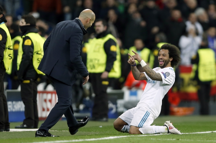 Real Madrid's Marcelo celebrates his side's 3rd goal with his head coach Zinedine Zidane during a Champions League Round of 16 first leg soccer match between Real Madrid and Paris Saint Germain at the Santiago Bernabeu stadium in Madrid, Spain, Wednesday, Feb. 14, 2018. (AP Photo/Francisco Seco)