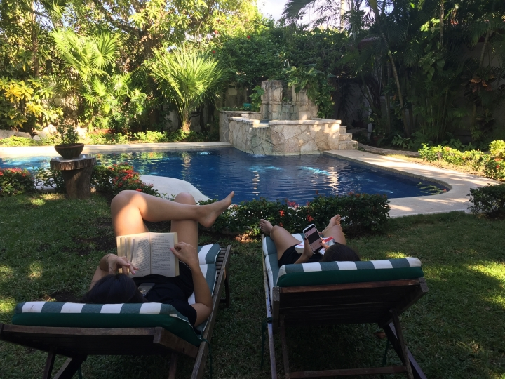This Dec. 24, 2017 photo taken in Cozumel, Mexico shows people relaxing by the pool in the yard of their Airbnb rental. Mexico is a popular vacation destination for winter and spring. But big decisions await travelers, especially those uninterested in the all-inclusive resorts that Cancun is known for. (AP Photo/Marjorie Miller)