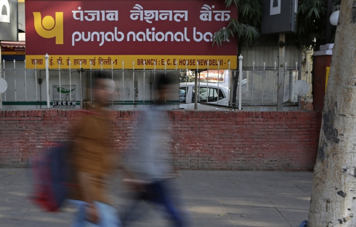 Pedestrians walk past a sign board of Punjab National Bank in New Delhi, India, Thursday, Feb. 15, 2018. State-owned Punjab National Bank has said in a statement that fraudulent transactions totaling $1.8 billion had been discovered in a Mumbai bank branch. Indian media outlets have linked the scam to jeweler Nirav Modi. (AP Photo/Altaf Qadri)
