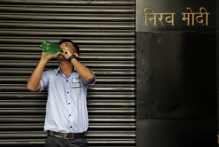 "A security guard drinks water outside a Nirav Modi jewelry boutique, in Mumbai, India, Thursday, Feb. 15, 2018. India is investigating an alleged $1.8 billion bank fraud, with the wealthy jeweler reportedly using fake bank documents to obtain overseas loans. Hindi on top right reads, ""Nirav Modi"". (AP Photo/Rajanish Kakade)"