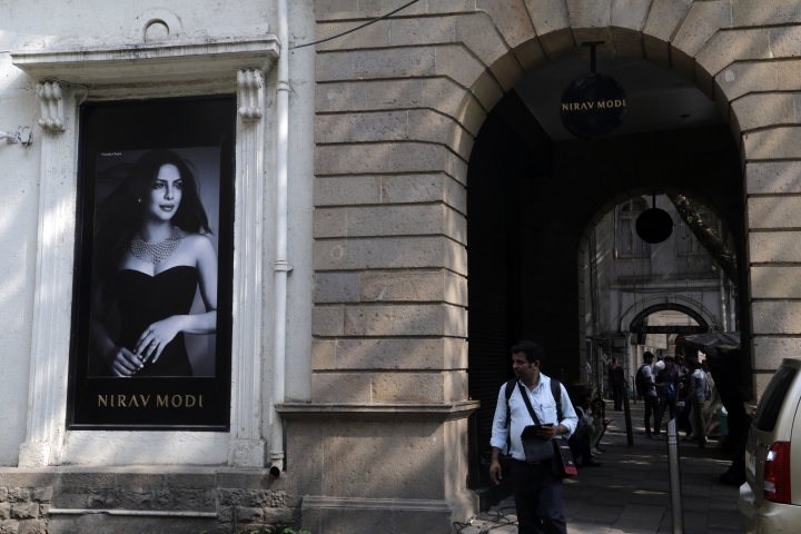 A man walks in front of a Nirav Modi jewelry boutique, that displays a black and white photograph of Bollywood actress Priyanka Chopra in Mumbai, India, Thursday, Feb. 15, 2018. India is investigating an alleged $1.8 billion bank fraud, with the wealthy jeweler reportedly using fake bank documents to obtain overseas loans. (AP Photo/Rajanish Kakade)