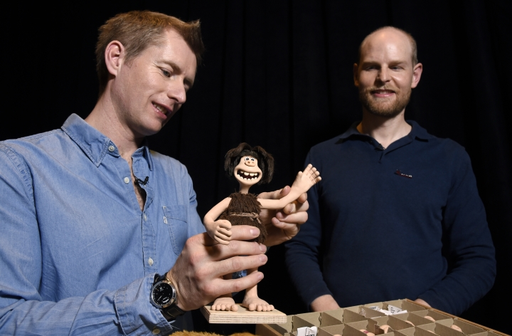 "Merlin Crossingham, left, and Will Becher, animation directors for the stop-motion animated film ""Early Man,"" demonstrate a waving motion for the puppet character Dug during an interview at the Beverly Hilton in Beverly Hills, Calif. The film opens nationwide on Friday, Feb. 16. (Photo by Chris Pizzello/Invision/AP)"