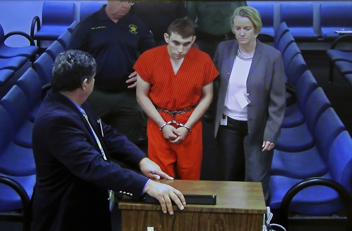 A video monitor shows school shooting suspect Nikolas Cruz, left, with public defender Melisa McNeille, making an appearance before Judge Kim Theresa Mollica in Broward County Court, Thursday, Feb. 15, 2018, in Fort Lauderdale, Fla. Cruz is accused of opening fire Wednesday at the school killing more than a dozen people and injuring several. (Susan Stocker/South Florida Sun-Sentinel via AP, Pool)