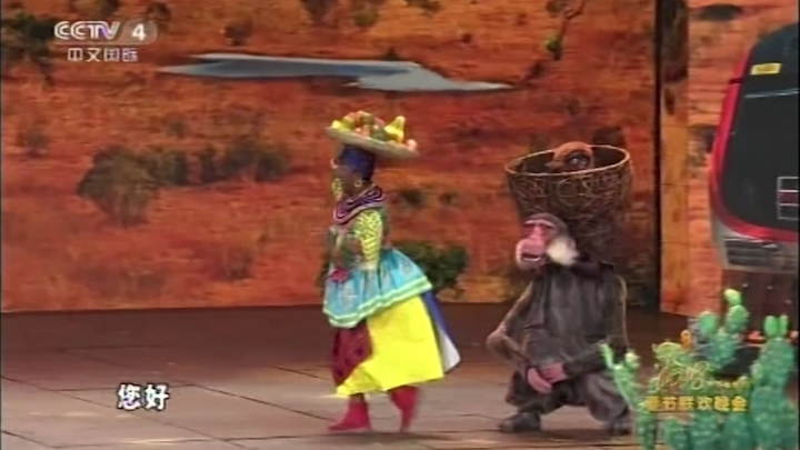 This is a screen grab take from CCTV China on Friday Feb. 16, 2018 showing dance sequence in an Africa skit shown on state television showing an Asian woman blacked up and someone dressed in a monkey costume. The Chinese comedy sketch broadcast on state media showing an Asian woman with her face blacked up has drawn accusations of racism. The skit was shown on state broadcaster CCTV on Thursday night and depicted the opening of a Chinese-built high-speed rail in Kenya. (CCTV via AP)