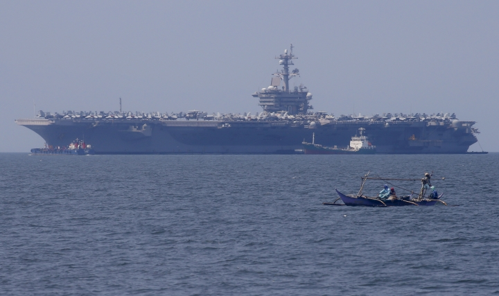 Fishermen on board a small boat pass by the USS Carl Vinson aircraft carrier at anchor off Manila, Philippines, for a five-day port call along with guided-missile destroyer USS Michael Murphy, Saturday, Feb. 17, 2018. U.S. Lt. Cmdr. Tim Hawkins told The Associated Press that American forces will continue to patrol the South China Sea wherever international law allows when asked if China's newly built islands could restrain them in the disputed waters. (AP Photo/Bullit Marquez)