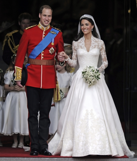 FILE - In this Friday, April, 29, 2011 file photo, Britain's Prince William and his wife Kate, Duchess of Cambridge stand outside Westminster Abbey after their Royal Wedding in London. With Prince Harry and Meghan Markle's May 19 wedding fast approaching, the fashion and bridal worlds are abuzz with talk of who the bride will pick to design her dress and what kind of look she would go for. (AP Photo/Martin Meissner, File)