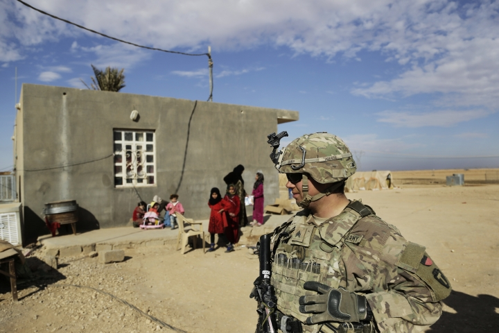 In this Jan. 27, 2018, photo, U.S. Army soldiers speak to families in rural Anbar on a reconnaissance patrol near a coalition outpost in western Iraq. A few hundred American troops are stationed at a small outpost near the town of Qaim along Iraq's border with Syria. Thousands of U.S. troops and billions of dollars spent by Washington helped bring down the Islamic State group in Iraq, but many of the divisions and problems that helped fuel the extremists' rise remain. (AP Photo/Susannah George)