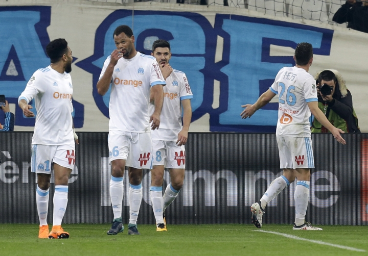 Marseille's Florian Thauvin, right, celebrates with supporters and his teammates after scoring, during the League One soccer match between Marseille and Bordeaux, at the Velodrome stadium, in Marseille, southern France, Sunday, Feb. 18, 2018. (AP Photo/Claude Paris)