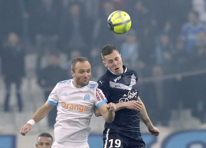 Marseille's Valere Germain, left, challenges for the ball with Bordeaux's Lukas Lerager, during the League One soccer match between Marseille and Bordeaux, at the Velodrome stadium, in Marseille, southern France, Sunday, Feb. 18, 2018. (AP Photo/Claude Paris)