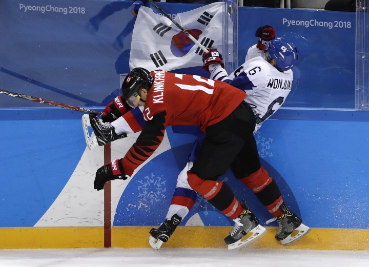 Rob Klinkhammer (12), of Canada, checks Kim Won-jun (6), of South Korea, during the third period of the preliminary round of the men's hockey game at the 2018 Winter Olympics in Gangneung, South Korea, Sunday, Feb. 18, 2018. (AP Photo/Matt Slocum)