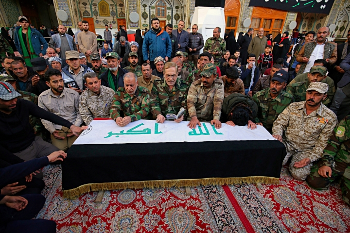 Mourners pray over the flag-draped coffin of Ismail Mahmoud, 24, a fighter of the Popular Mobilization Forces, who was killed Sunday in an attack southwest of the northern city of Kirkuk, during his funeral in Najaf, Iraq, Monday, Feb. 19, 2018. Officials said Monday that Islamic State militants ambushed the group of Iraq's Shiite-led paramilitary fighters, killing Mahmoud and at least 26 others, more than two months after Baghdad declared victory over the extremist group. (AP Photo/Anmar Khalil)