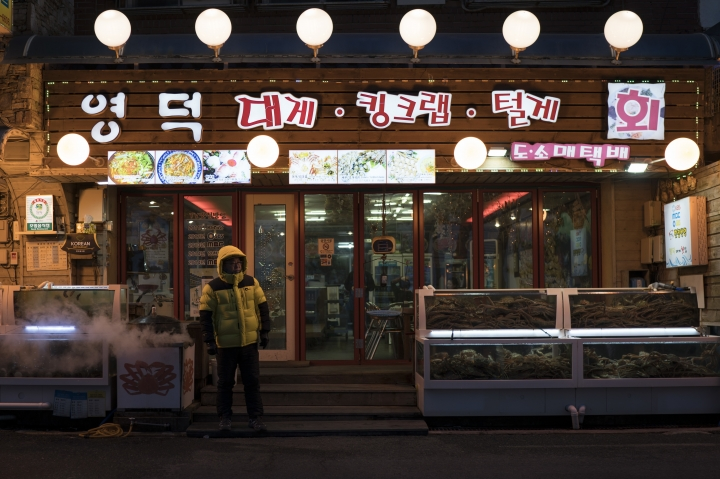 FILE - In this Feb. 4, 2018 file photo, a restaurant worker stands next to fish tanks as he waits for customers in Gangneung, South Korea. When it came to landing the 2018 Winter Games, the things that had always isolated the area - the heavy snows, long winters and sharp mountains that rise nearly half a mile above sea level - were a blessing. But when the visitors leave, many of the province's problems will remain. It will still have a tiny, rapidly aging population that's second to last in the nation in average income and without any real industry after the collapse of the mining and coal industries that many once relied on. (AP Photo/Felipe Dana, File)
