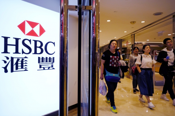 People walk past a HSBC local branch in Hong Kong Tuesday, Feb. 20, 2018. HSBC says its annual pretax profits by 11 percent on strong earnings from Asia, in the latest sign that the London-based global bank's restructuring to focus even more on the region reaps further dividends. (AP Photo/Vincent Yu)
