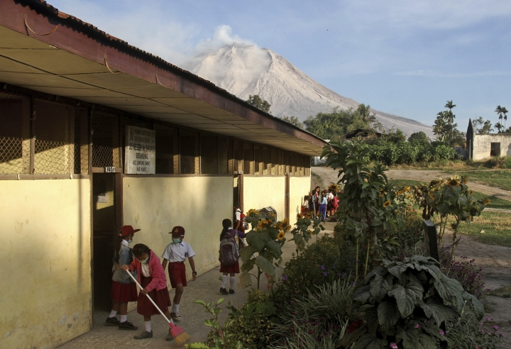 "Students prepare before the start of their class as Mount Sinabung is seen in the background, at an elementary school in Beganding, North Sumatra, Indonesia, Tuesday, Feb. 20, 2018. Volcanologists say Monday's eruption of the volcano that shot ash 5 kilometers (3 miles) high also ""annihilated"" the mountain's summit. (AP Photo/Ahmad Putra)"
