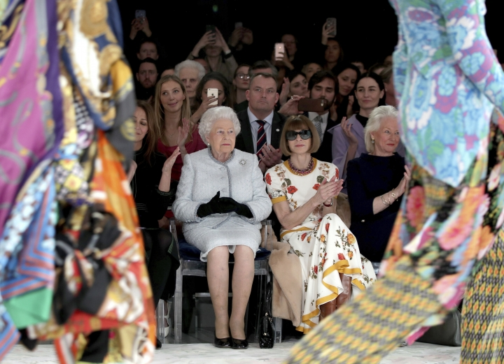 Britain's Queen Elizabeth, second left, sits next to fashion editor Anna Wintour, third left, and Caroline Rush, chief executive of the British Fashion Council (BFC), left, as they view Richard Quinn's runway show before presenting him with the inaugural Queen Elizabeth II Award for British Design, as she visits London Fashion Week's BFC Show Space in central London, Tuesday, Feb. 20, 2018. (Yui Mok/Pool photo via AP)