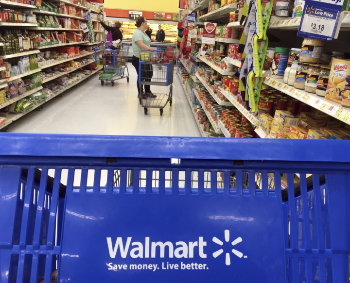 FILE- In this June 5, 2017, file photo, customers shop for food at Walmart in Salem, N.H. Walmart reports financial results Tuesday, Feb. 20, 2018. (AP Photo/Elise Amendola, File)