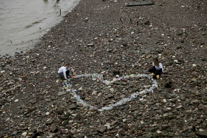 Volunteers pose for photographers with a Valentine's Day love heart shaped collection of plastic bottles they and others made from bottles that were lying washed up nearby during a media event organised by the #OneLess campaign and Thames21 London waterways charity to promote public awareness of the single-use plastic bottles that end up in the Thames River and wash up on in places like this location, the foreshore at the site of the ancient and no-longer used Queenhithe dock, on the north bank of the River Thames in London, Friday, Feb. 9, 2018. Amid growing evidence of dire amounts of waste in the world's oceans, conservation is becoming a selling point for firms trying to jump on the bandwagon of concern about the flood of plastic choking sea life. (AP Photo/Matt Dunham)