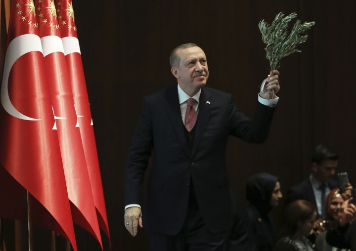 Turkey's President Recep Tayyip Erdogan, holding an olive branch arrives to deliver a speech at an event in Ankara, Turkey, Tuesday, Feb. 20, 2018. Erdogan said Turkish troops involved in the month-long offensive, codenamed 'Operation Olive Branch', to drive out Syrian Kurdish militiamen from a northwestern Syrian enclave will soon begin a siege of the city of Afrin. (Pool Photo via AP)