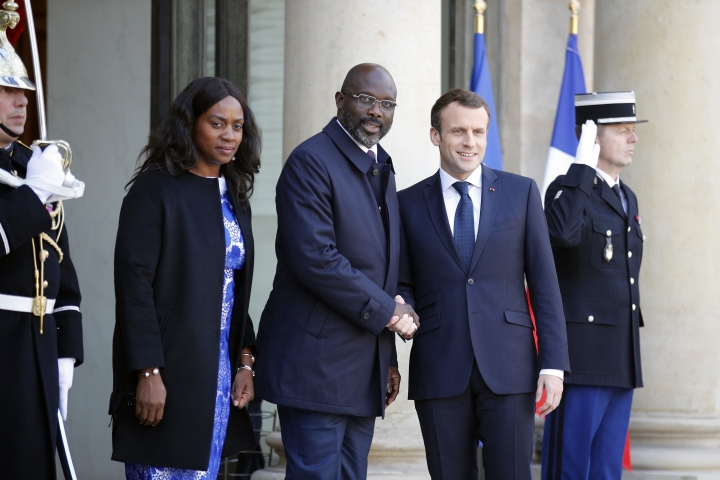 French President Emmanuel Macron welcomes Liberia's recently-elected President George Weah, flanked with his wife Clar Weah upon their arrival at the Elysee Palace, in Paris, France, Wednesday, Feb. 21, 2018. The French presidency said discussions will notably focus on launching a fund dedicated to sports projects in Africa. (AP Photo/Francois Mori)
