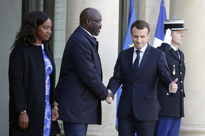 French President Emmanuel Macron welcomes Liberia's recently-elected President George Weah, as his wife Clar Weah looks on, upon their arrival at the Elysee Palace, in Paris, France, Wednesday, Feb. 21, 2018. The French presidency said discussions will notably focus on launching a fund dedicated to sports projects in Africa. (AP Photo/Francois Mori)