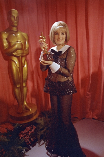 "FILE - In this April 14, 1969 file photo, actress and singer Barbra Streisand wears a sequined Arnold Scaasi bell-bottomed sheer pantsuit as she poses with her Oscar for her role in ""Funny Girl"" at the 41st Academy Awards in Los Angeles. (AP Photo/George Birch, File)"