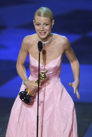 """FILE - In this March 21, 1999 file photo, Gwyneth Paltrow, wearing a soft pink by Ralph Lauren gown, accepts the Oscar for best actress for her role in """"Shakespeare In Love"""" during the 71st Annual Academy Awards in Los Angeles. (AP Photo/Eric Draper, File)"""