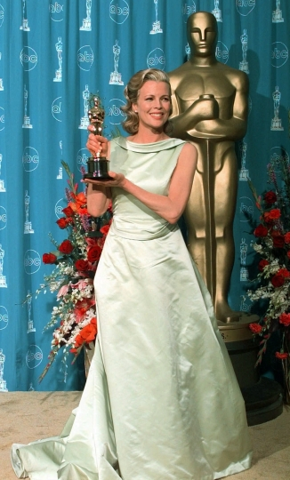 """FILE - In this March 23, 1998 file photo, Kim Basinger wears an Escada gown as she holds the Oscar for best supporting actress for her role in """"L.A. Confidential,"""" at the 70th Academy Awards in Los Angeles. (AP Photo/Mark J. Terrill, File)"""