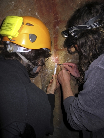 In this undated image provided by João Zilhão in February 2018, Dirk Hoffmann and Alistair Pike take a sample from a calcite crust on top of a red ladder-shaped cave painting in La Pasiega in Puente Viesgo, Spain. New discoveries in some Spanish caves give the strongest evidence yet that Neanderthals created art. (João Zilhão via AP)