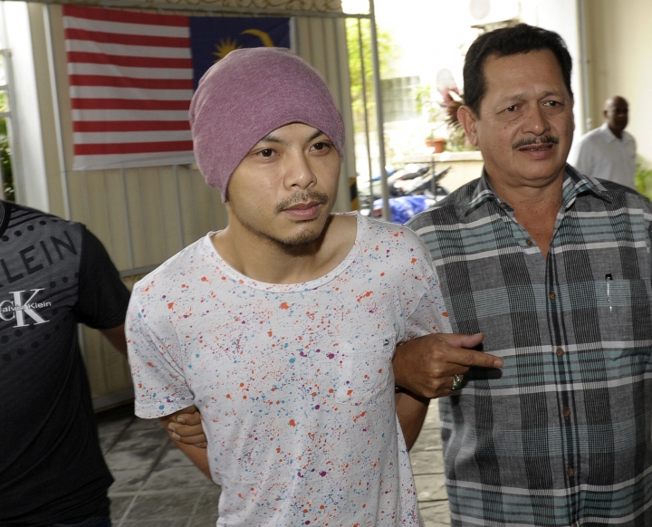 "FILE - In this Aug. 22, 2016, file photo, Wee Meng Chee, left, a Malaysian rapper popularly known as Namewee, is escorted by plainclothes policemen on his arrival at the magistrate court in Penang, Malaysia. Malaysian police said in a statement that Wee was detained Thursday, Feb. 23, 2018 after they received four public complaints that his video marking the Chinese year of the dog had ""insulted Islam and could negatively impact racial unity and harmony."" (AP Photo/Gary Chuah, File)"