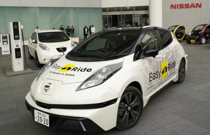 """In this Wednesday, Feb. 21, 2018, photo, Nissan Motor Co.'s Easy Ride robo-vehicle starts going from its global headquarters in Yokohama, near Tokyo. Starting next month, Nissan is testing on regular roads what it calls """"a robo-vehicle mobility service."""" Called Easy Ride, it uses a cell-phone app to book semi-autonomous driven rides. (AP Photo/Shizuo Kambayashi)"""