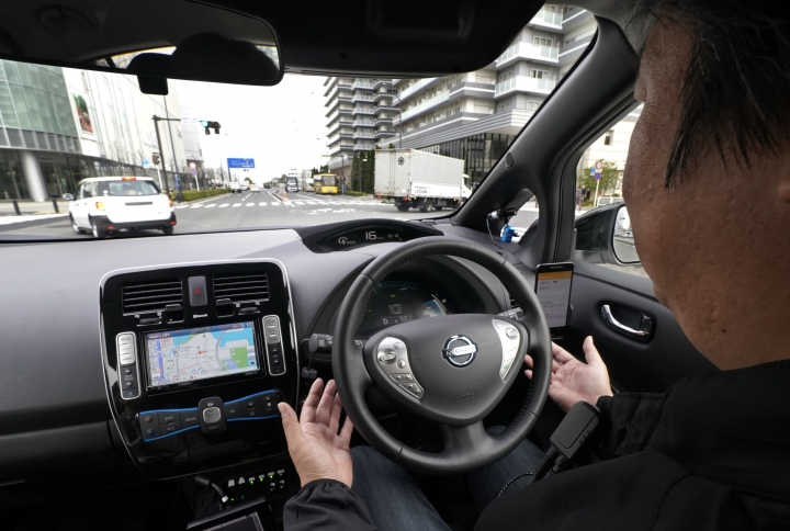 """In this Wednesday, Feb. 21, 2018, photo, a Nissan Motor Co. staff member gets his hands off of the steering wheel of its Easy Ride robo-vehicle during a test ride on a course in Yokohama, near Tokyo. Starting next month, Nissan is testing on regular roads what it calls """"a robo-vehicle mobility service."""" Called Easy Ride, it uses a cell-phone app to book semi-autonomous driven rides. (AP Photo/Shizuo Kambayashi)"""
