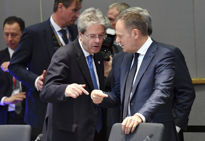 Italian Prime Minister Paolo Gentiloni, left, speaks with European Council President Donald Tusk during a round table at an EU summit at the Europa building in Brussels on Friday, Feb. 23, 2018. European Union leaders meet without Britain Friday looking to plug a major budget hole after Brexit and endorse a plan to streamline the European Parliament by sharing out the country's seats. (AP Photo/Geert Vanden Wijngaert)