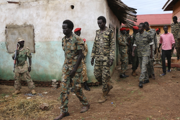 """FILE - In this Tuesday, May 30, 2017 file photo, South Sudanese soldiers accused of gang-raping five foreigners, murdering a local journalist and looting a hotel, are led to their prison van after attending a hearing of their trial in the capital Juba, South Sudan. The latest report on human rights abuses in South Sudan's five-year civil war, released by a United Nations commission Friday, Feb. 23, 2018 says it has identified more than 40 senior military officials """"who may bear individual responsibility for war crimes."""" (AP Photo/Bullen Chol, File)"""