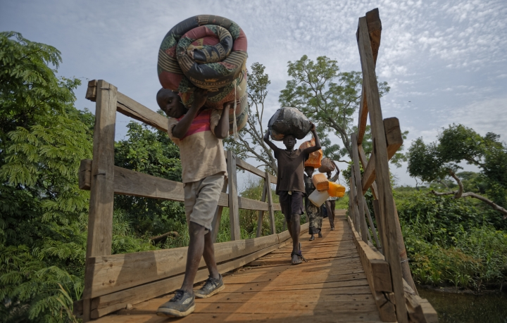 """FILE - In this Thursday, June 8, 2017 file photo, from left to right, South Sudanese refugees Thomas Wani, 12, brother Peter Lemi, 14, mother Rose Sunday, and father Julius Lezu, cross a wooden bridge from South Sudan to Uganda at the Busia crossing, near Kuluba, in northern Uganda. The latest report on human rights abuses in South Sudan's five-year civil war, released by a United Nations commission Friday, Feb. 23, 2018 says it has identified more than 40 senior military officials """"who may bear individual responsibility for war crimes."""" (AP Photo/Ben Curtis, File)"""