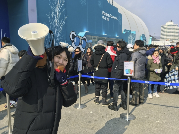 In this Thursday, Feb. 22, 2018 photo, an employee gives directions to Olympic fans waiting in line at the giant gift shop at Pyeongchang Olympic Park during the 2018 Winter Olympics in Pyeongchang, South Korea. The 2018 Winter Olympics may be remembered for many things. The extreme cold during week one. North Koreans participating. Russians here but not under their own flag. And then there is the odd mix of souvenirs and the enormous lines to buy them. (AP Photo/Scott Mayerowitz)