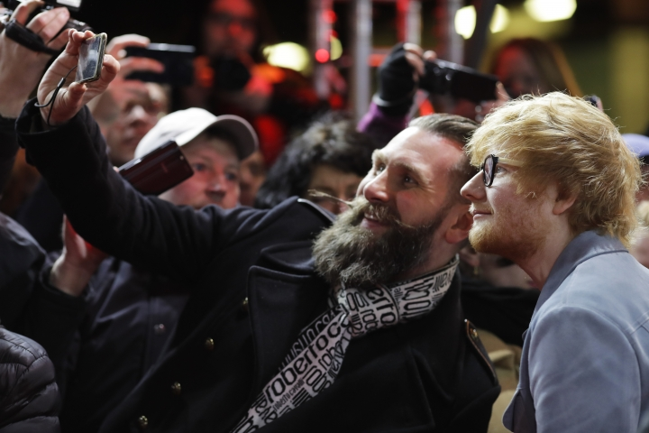 Singer-songwriter Ed Sheeran, right, poses for a photo with a fan as he arrives for the screening of the film 'Songwriter' during the 68th edition of the International Film Festival Berlin, Berlinale, in Berlin, Germany, Friday, Feb. 23, 2018. (AP Photo/Markus Schreiber)