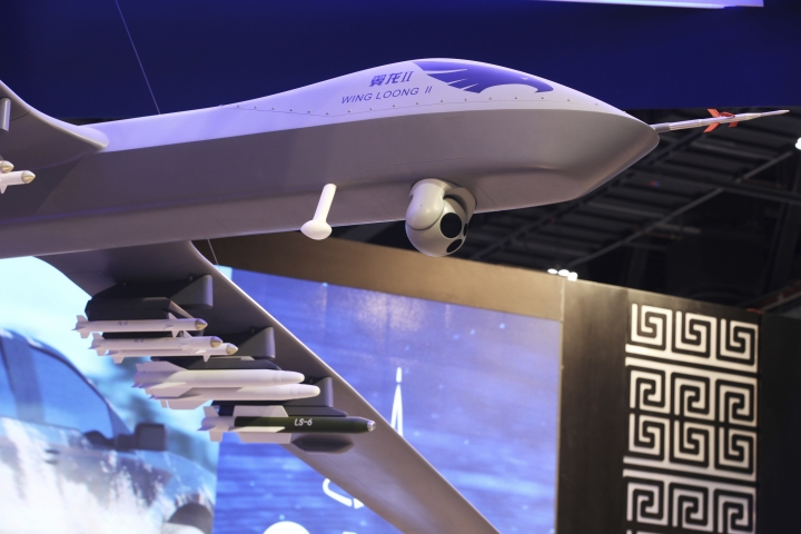 A model of a Wing Loong II weaponized drone hangs above the stand for the China National Aero-Technology Import & Export Corp. at a military drone conference in Abu Dhabi, United Arab Emirates, Sunday, Feb. 25, 2018. The United Arab Emirates on Sunday opened a stand-alone trade show featuring military drones called the Unmanned Systems Exhibition & Conference, showing the power the weapons have across the Middle East. (AP Photo/Jon Gambrell)