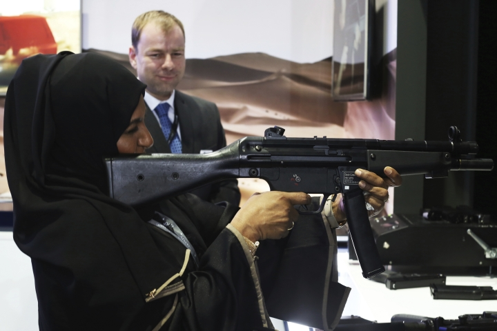 A woman fires an HK MP5 submachine gun in a simulator by Saab at a drone conference in Abu Dhabi, United Arab Emirates, Sunday, Feb. 25, 2018. The United Arab Emirates on Sunday opened a stand-alone trade show featuring military drones called the Unmanned Systems Exhibition & Conference, showing the power the weapons have across the Middle East. (AP Photo/Jon Gambrell)
