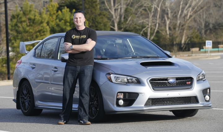 In this Friday, Feb. 9, 2018, photo, Jonathan Cypert stands in front of his wife's 2017 Subaru Impreza, in Virginia, that he purchased with bitcoins he acquired in 2011. Cypert sees his bitcoin cache as a nest egg to tide him over after he retires from the military. (AP Photo/Steve Helber)