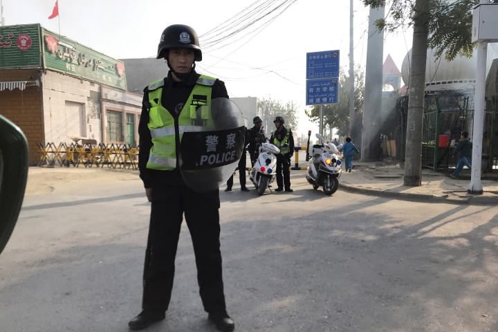 FILE - In this Nov. 2, 2017, file photo, a police personnel holding shield and baton guards a security post leading into a center believed to be used for re-education in Korla in western China's Xinjiang region. Human Rights Watch says it has found new evidence that authorities in one of China's most repressive regions are sweeping up citizens' personal information in a stark example of how modern big-data technology can be applied to policing, and potentially abused. (AP Photo/Ng Han Guan, File)