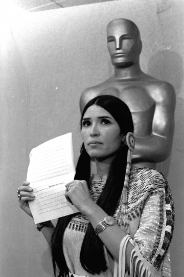 "FILE - In this March 27, 1973 file photo, Sacheen Littlefeather, tells the audience at the Academy Awards ceremony that Marlon Brando was declining to accept his Oscar as best actor for his role in ""The Godfather."" The move was meant to protest Hollywood's treatment of American Indians. (AP Photo, File)"