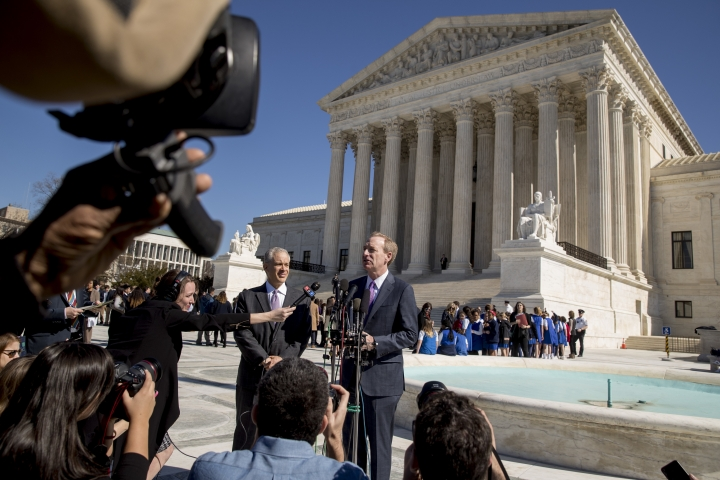 Microsoft President and Chief Legal Officer Brad Smith, accompanied by attorney Josh Rosenkranz, center left, speaks to reporters outside the Supreme Court, Tuesday, Feb. 27, 2018 in Washington. The Supreme Court heard arguments Tuesday in a dispute between the Trump administration and Microsoft Corp. over a warrant for emails that were sought as part of a drug trafficking investigation.(AP Photo/Andrew Harnik)