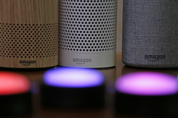 FILE - In this Sept. 27, 2017, file photo, Amazon Echo and Echo Plus devices, behind, sit near illuminated Echo Button devices during an event announcing several new Amazon products by the company in Seattle. Amazon is expanding its home-security business by buying Ring, the maker of Wi-Fi-connected doorbells. The deal comes months after the online retailer started selling its own Wi-Fi-connected indoor security cameras, which work with its voice-assistant Alexa. (AP Photo/Elaine Thompson, File)