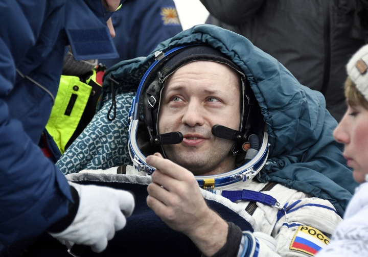 Russian cosmonaut Alexander Misurkin rests in a chair after landing in a remote area south-east of the Kazakh town of Zhezkazgan, Kazakhstan, Wednesday, Feb. 28, 2018. Three astronauts returned from the International Space Station to the snowy, bitingly cold flat lands of Central Asia, ending a 5 1/2-month mission highlighted by robotic renovations, schoolteacher pep talks and heavenly greetings from Pope Francis. (Alexander Nemenov/Pool Photo via AP)