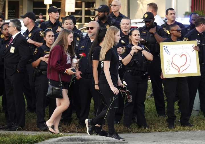 Students carrying flowers walk past police on their way to Marjory Stoneman Douglas High School in Parkland, Fla., Wednesday, Feb. 28, 2018. With a heavy police presence, classes resumed for the first time since several students and teachers were killed by a former student on Feb. 14. (Joe Cavaretta/South Florida Sun-Sentinel via AP)