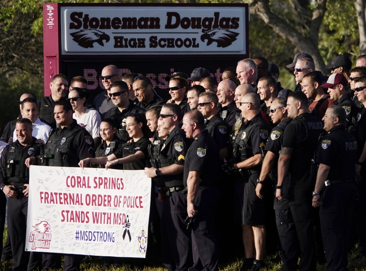 Police pose for a photo after they escorted returning students to Marjory Stoneman Douglas High School in Parkland, Fla., Wednesday, Feb. 28, 2018. With a heavy police presence, classes resumed for the first time since several students and teachers were killed by a former student on Feb. 14. (Joe Cavaretta/South Florida Sun-Sentinel via AP)