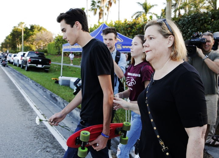 "Marjory Stoneman Douglas High School student David Hogg, left, walks to class for the first time since a former student opened fire there with an assault weapon, Wednesday, Feb. 28, 2018, in Parkland, Fla. ""This is a picture of education in fear in this country. The NRA wants more people just like this, with that exact firearm to scare more people and sell more guns,"" said Hogg, who has become a leading voice in the students' movement to control assault weapons .(AP Photo/Terry Renna)"