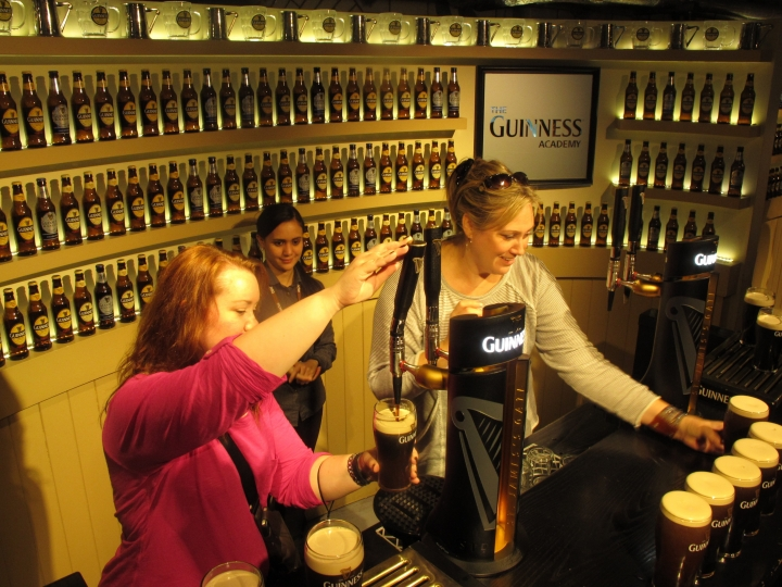 """FILE - In this Sept. 24, 2014, file photo, two tourists attempt to pour the perfect pint during a visit to the Guinness Storehouse in Dublin, Ireland. Visitors are given a choice between drinking their complimentary pint whether they pour it themselves or receive it from a bartender in the Storehouse's rooftop pub. Think of beer and you may think of Irish pubs or Germany's Oktoberfest. But a book called the """"Atlas of Beer,"""" written by two geographers, surveys beer across six continents, from banana beer in Tanzania to the booming microbrewery and craft beer movement in the U.S. (AP Photo/Shawn Pogatchnik, File)"""