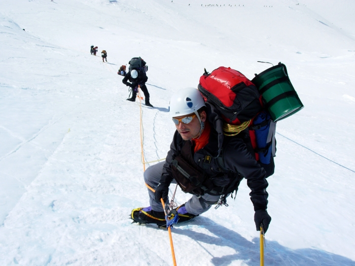 In this May 2007 photo provided by Clean Mountain Can, Matt Anderson, a guide and mountain climber, carries a green Clean Mountain Can, a portable toilet, on his backpack as he ascends Denali in Alaska along the West Buttress Route. The National Park Service is considering revised rules for climbers that would require human waste to be deposited in a crevasse at 14,200 feet or at the Talkeetna, Alaska, ranger station. Current rules allow climbers below 15,000 feet to deposit waste into other deep crevasses but research indicates the glacier at lower elevations may not render it inert. (Coley Gentzel/Clean Mountain Can via AP)